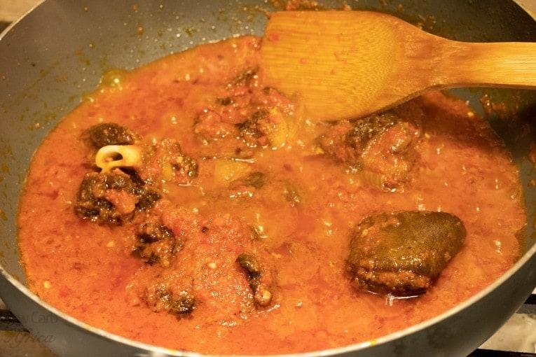Making efo riro, add goat meat and mushrooms